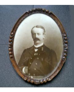 Portretfoto van een marineofficier in ovale notenhouten lijst, ca. 1900