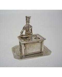 Zilveren miniatuur, kok bij fornuis
