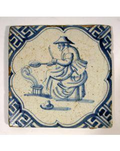 Figuurtegel, vrouw die pannenkoeken bakt, 17e eeuw
